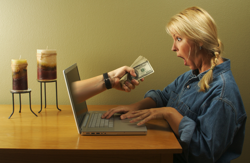 woman being handed money from laptop screen