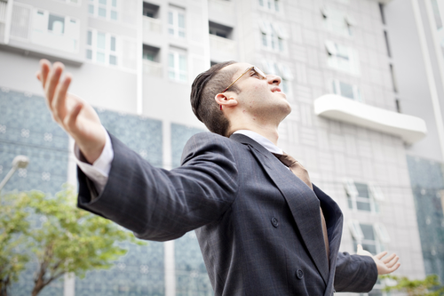 man in business suit with outstretched arms