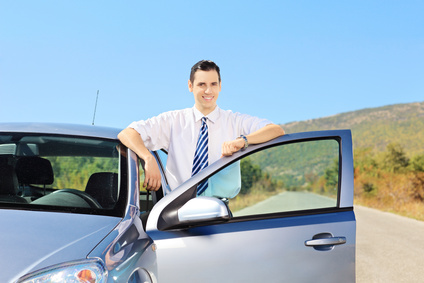 Smiling young male with tie posing next to his car