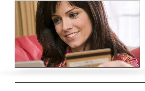 woman with a laptop and holding a credit card