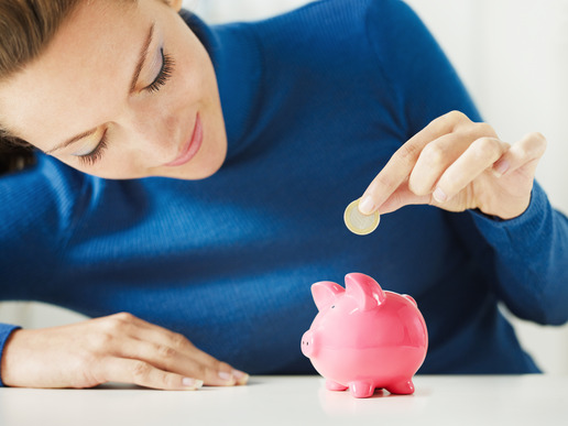 woman putting a coin in a piggy bank
