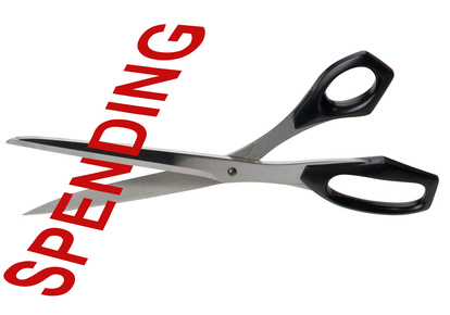Pair of scrissors cutting the word Spending