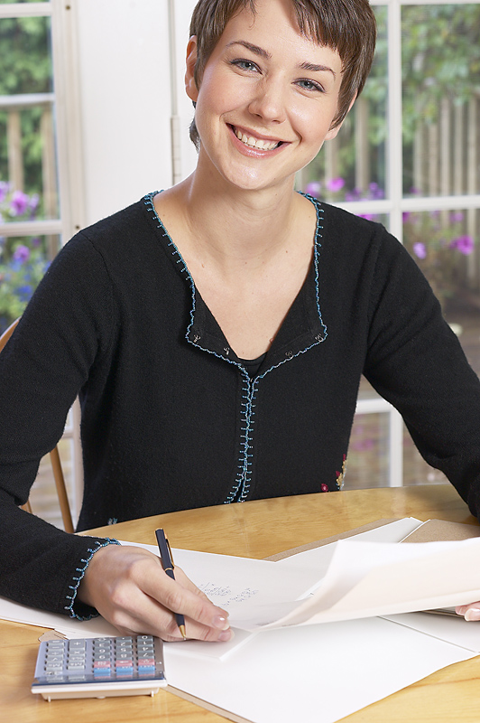 Smiling woman with pen, paper, calculator