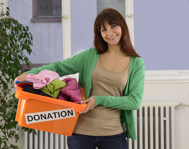 Woman holding basket of clothing labeled Donation